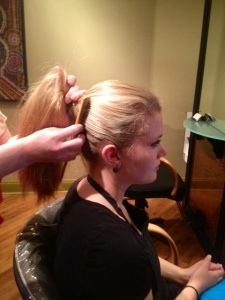 Holding hair in a high pony, comb stray hairs back toward pony, then spray again ...